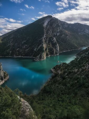 Beautiful & calm emerald river, before a mountain & a forest nearby in Catalunya, spain