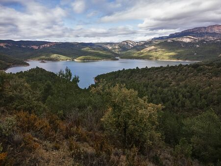 A beautiful wide shot of a small lake surrounded by trees & come clouds in Catalunya, spain