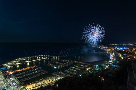 Awesome wide angle shot of fireworks above the Blanes in Catalonia, Spain lighting the coast waters beside the enlightened city & dock 写真素材