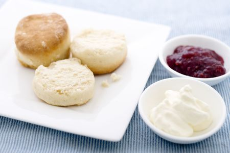 Scones with jam and cream on blue tablecloth