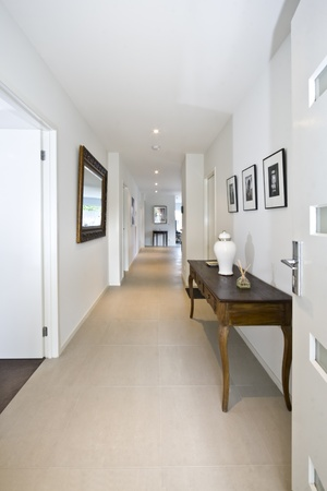 hallway: An open front door welcoming you into a stylish contemporary new home entrance area. Stock Photo