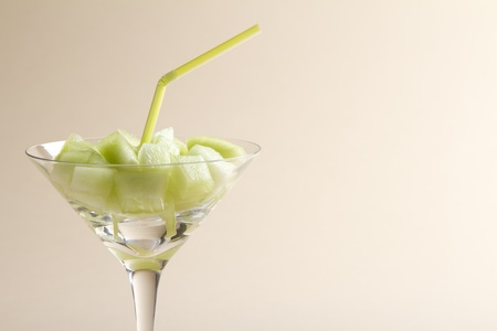 Pieces of honeydew green melon in a martini glass with straw on a beige background
