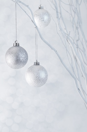 Christmas silver baubles hanging on white twig arrangement with sparkle background vertical