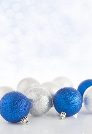 Blue and silver christmas baubles on a sparkly bokeh background Stock Photo