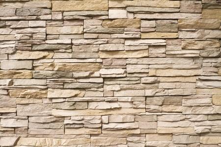 Hintergrund eines zeitgenössischen gestapelten Steinmauer in warmen Brauntönen Standard-Bild