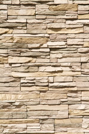 Stacked stone wall background of warm brown tones in vertical format Stock Photo