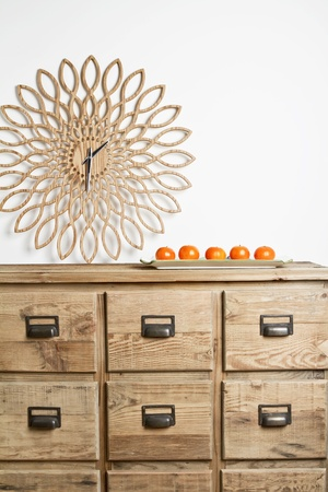 Earthy homewares clock and mandarins on a storage buffet