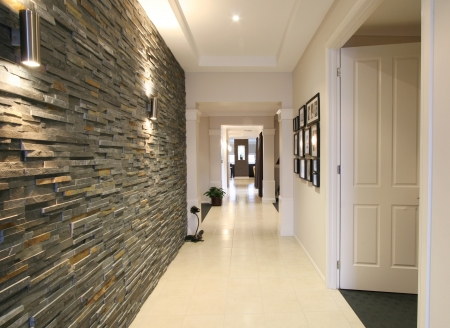 feature: Looking down the entrance hall of a contemporary new home with bluestone feature wall.