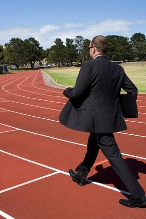 Business man walking on athletics running track photo