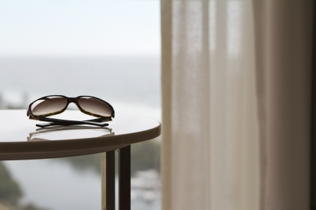 luxury hotel room: Sunglasses on a table in a luxury hotel room or apartment with blurred view of the ocean behind