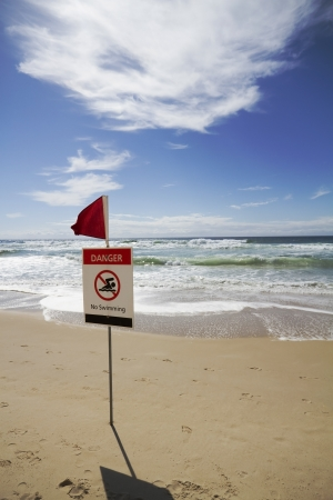 Rough surf beach at surfers paradise australia with danger sign