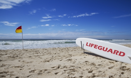 Lifeguard surfboard on the beach near a safe swimming flag