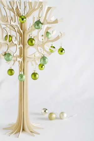 Stylised designer christmas tree made from bolser wood with green baubles Stock Photo