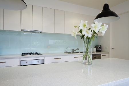 stone worktop: White lily flowers on contemporary kitchen island bench