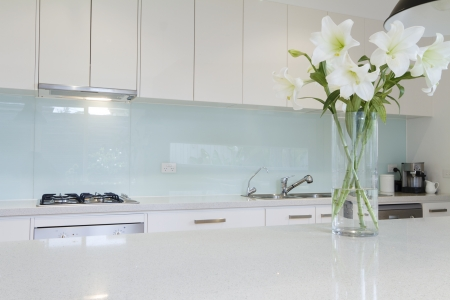 Flowers on white kitchen bench with splashback