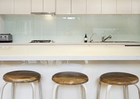 stone worktop: Kitchen benchtop, splashback and stools contemporary
