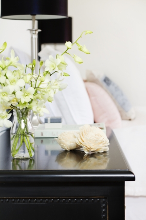 orchid house: Orchids in glass vase on pretty bedside table vertical Stock Photo