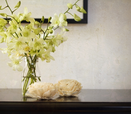 bunch up: Vintage rustic texture behind orchids in glass vase Stock Photo