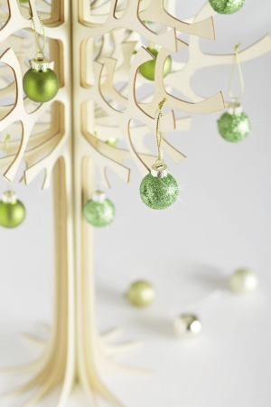 Small stylized wooden christmas tree made from bolder wood with green baubles
