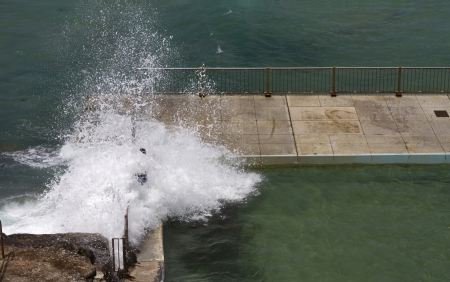 Dangerous waves breaking over edge of ocean rock pool
