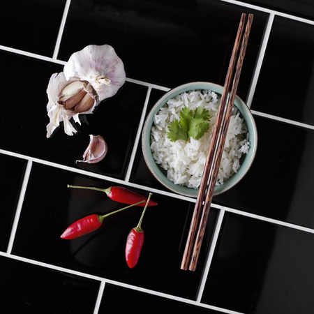 Contemporary angled overhead of asian rice and ingredients dark background