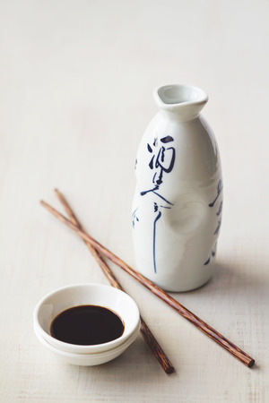 White japanese bottle and background with sauce bowl and chopsticks Stock Photo