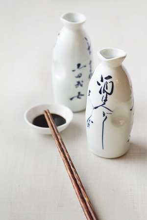 hoisin: Two white Asian style bottles with soy sauce bowl and chopsticks