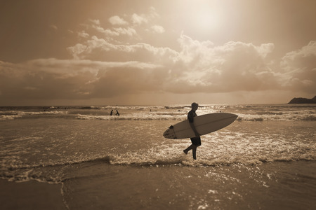 Backlit Early morning surfer walking on the beach with his board Stock Photo