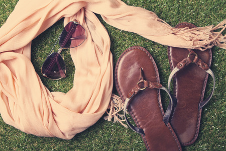neutrals: Spring or summer womens fashion accessories lying on grass