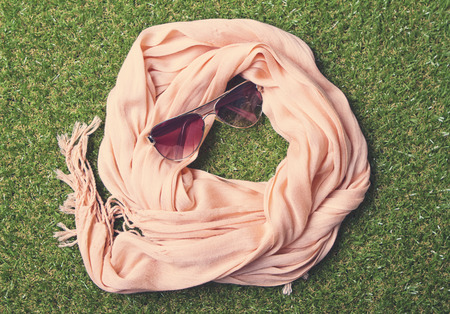 Overhead view of fashion scarf and sunglasses on grass