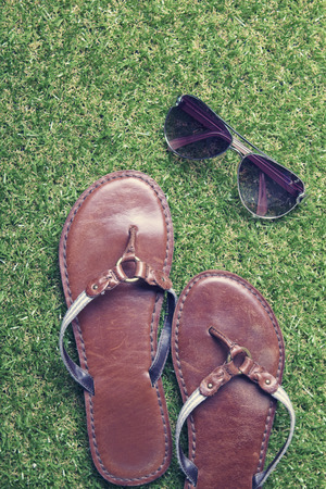 neutrals: Close up of summer sandals and sunglasses on grass