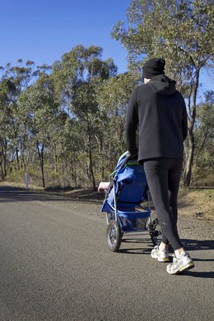Dad jogging or walking with baby stroller on a country road Stock Photo
