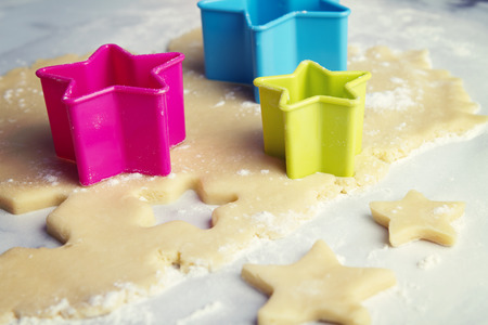 Cutting star shapes in cookie dough Stock Photo