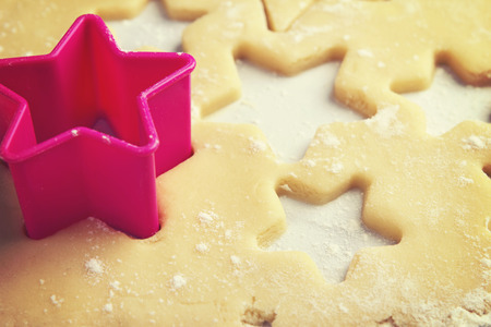 Close up of star shape pink cookie cutter in dough 스톡 콘텐츠