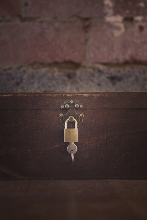 floorboards: Wooden padlocked box on floorboards and brick wall Stock Photo