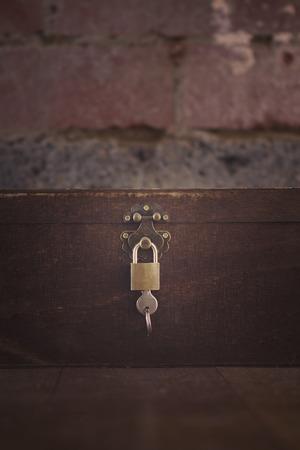 padlocked: Wooden padlocked box on floorboards and brick wall Stock Photo