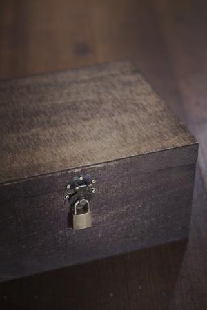 padlocked: Wooden padlocked box on floorboards overhead Stock Photo