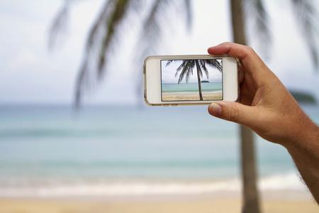 fiestas electronicas: Tel�fono m�vil de fotograf�a de una amplia visi�n horizontal de playa Foto de archivo
