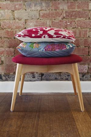 Docroative cushions on ottoman stool against rustic brick wall