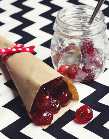 Glace cherries in paper cone vintage jar on chevron background photo