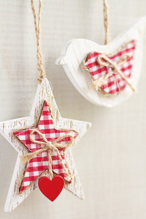 Home made crafty Christmas decorations hanging on white background vertical