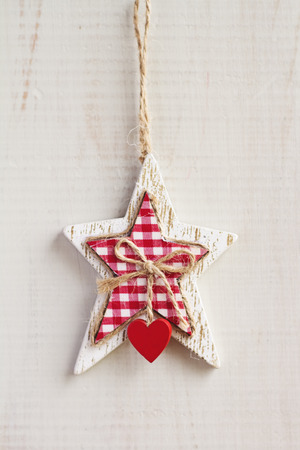 White craft star Christmas decoration hanging on white wooden background vertical