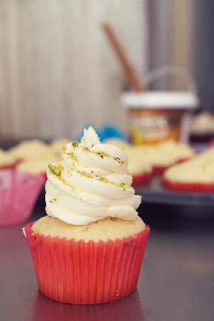 Vanilla pistachio gourmet cupcake with commercial kitchen in background