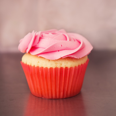 Single pink rose cupcake with blurred background
