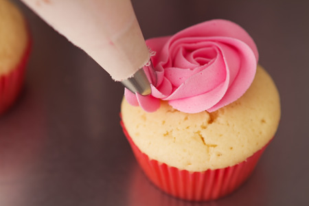 Close up pink rose frosted cupcake being iced Horizontal
