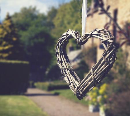 Heart of sticks hanging in beautiful wedding gardens