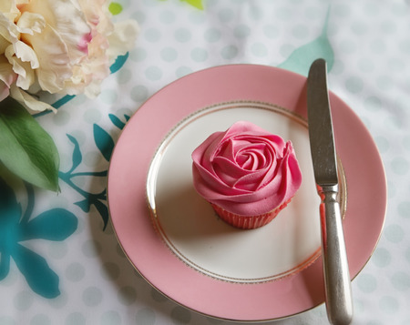 Overhead of pink rose frosted cupcake in vintage table setting