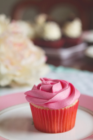 Pink vanilla rose cupcake with blurred cakes behind Archivio Fotografico