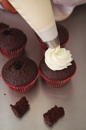 Whipped cream being piped onto chocolate cupcakes Stock Photo