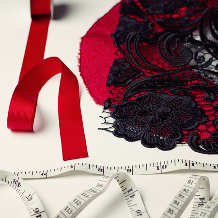 made to measure: Deconstructed red and black millinery materials and tape measure Stock Photo